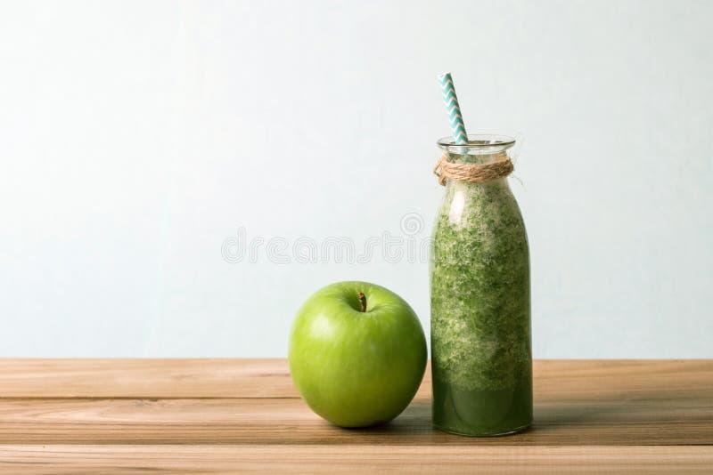 在玻璃瓶的健康新鲜的绿色圆滑的人汁在健康戒毒所和饮食习性概念的木桌上 库存照片