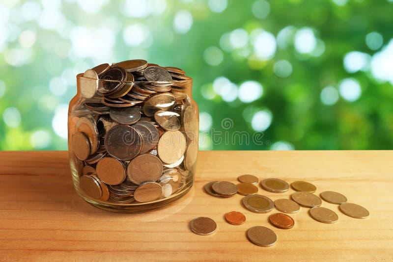 在玻璃瓶的攒钱在老木桌前景有被弄脏的绿色bokeh背景 免版税库存照片