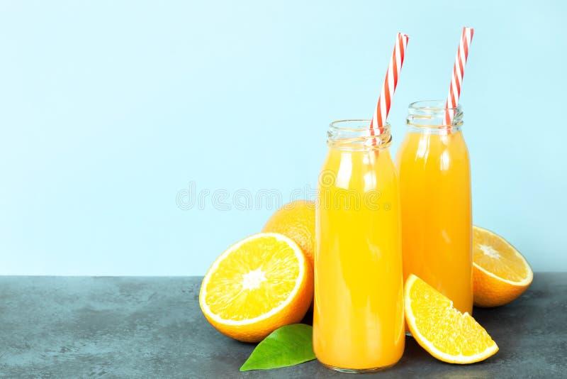 在玻璃瓶的新鲜的橙汁过去,在黑暗的桌上的新鲜的桔子 库存照片