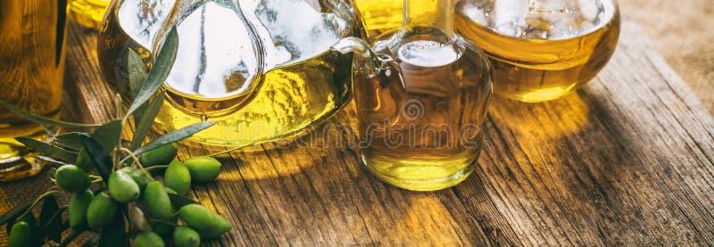 在玻璃瓶的橄榄油在木桌,横幅,特写镜头视图上 免版税库存图片