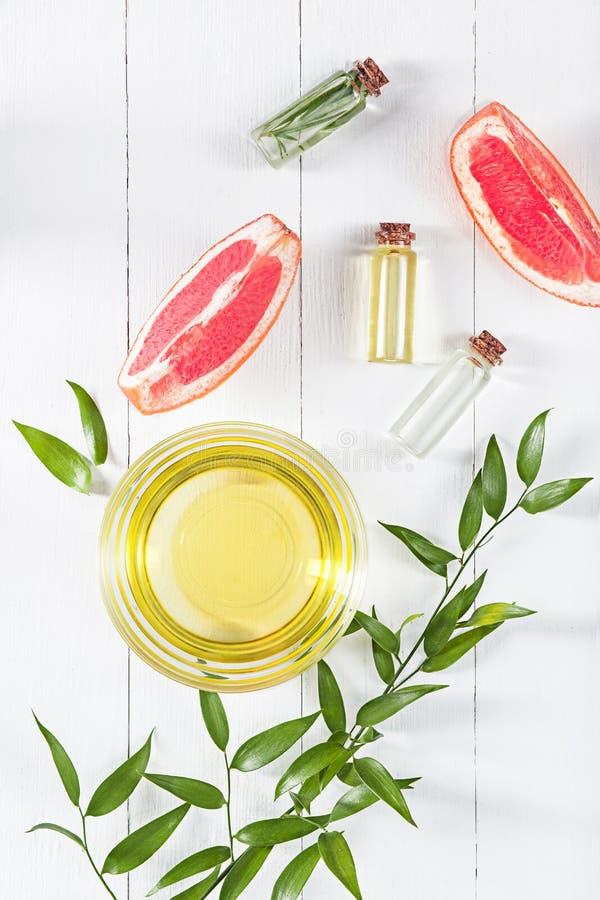 在玻璃瓶的精油用新鲜,水多的葡萄柚和绿色叶子秀丽治疗 免版税库存图片