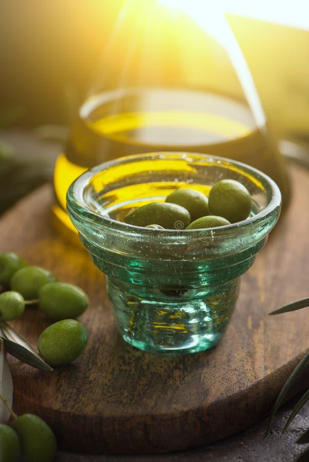 在玻璃瓶的额外处女橄榄油有杯子的在土气背景的橄榄 关闭 库存图片