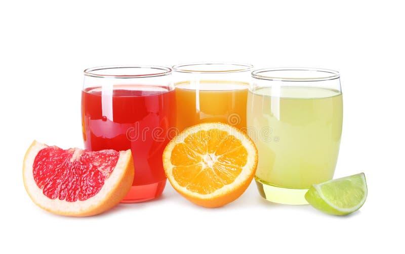在玻璃的不同的新柑橘饮料用在白色背景的被切的果子 免版税库存照片