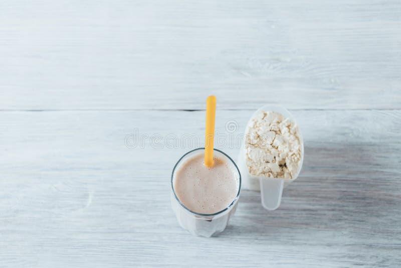 在玻璃的乳清蛋白震动与秸杆 免版税库存照片