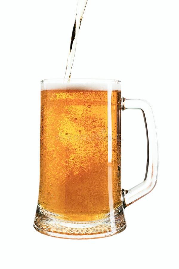 在玻璃的倾吐的低度黄啤酒 免版税库存照片