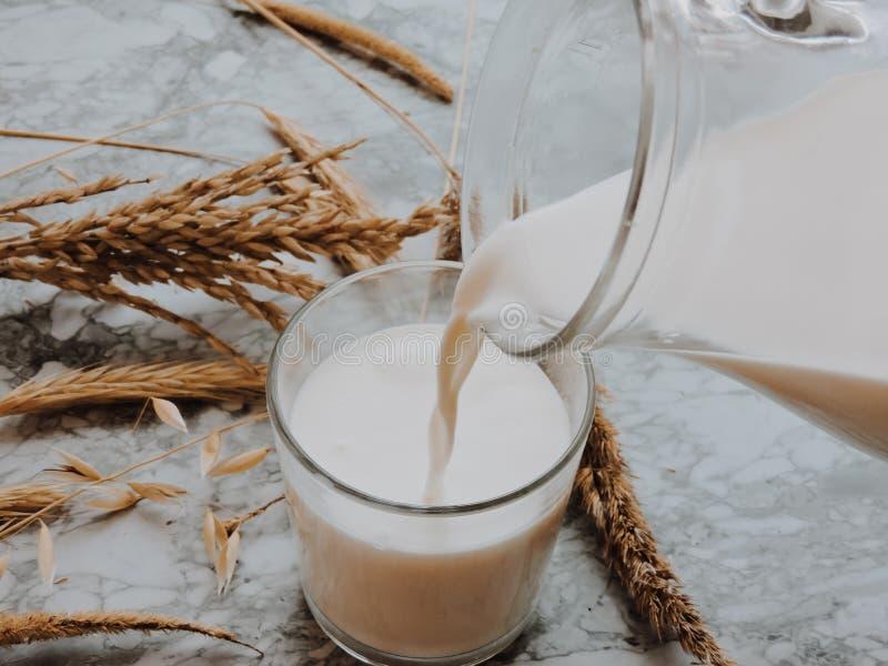 在玻璃的倾吐的牛奶在蓝色背景 倾吐新鲜的牛奶做冠飞溅 o 乳白玻璃顶视图 库存照片