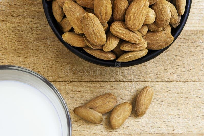 在玻璃的健康杏仁牛奶在一张木桌上用在陶瓷碗的杏仁 食物和饮料概念 免版税库存照片