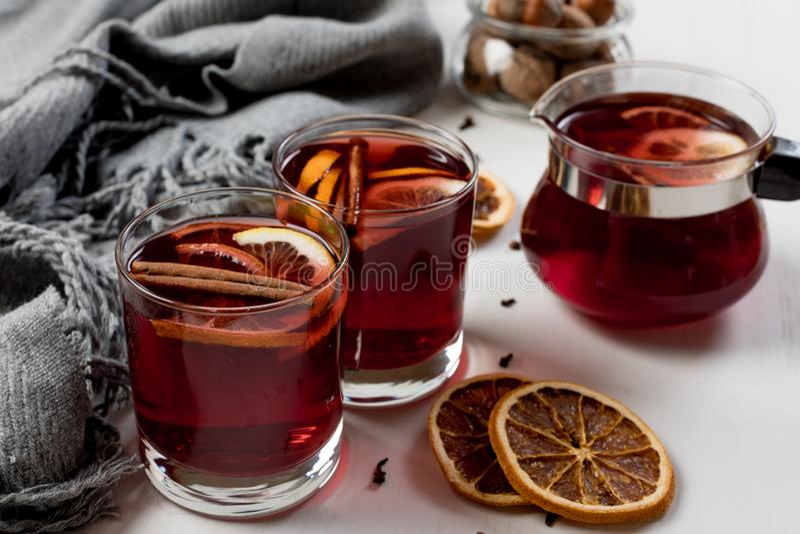 在玻璃的加香料的热葡萄酒用桔子和香料在灰色围巾附近 免版税图库摄影