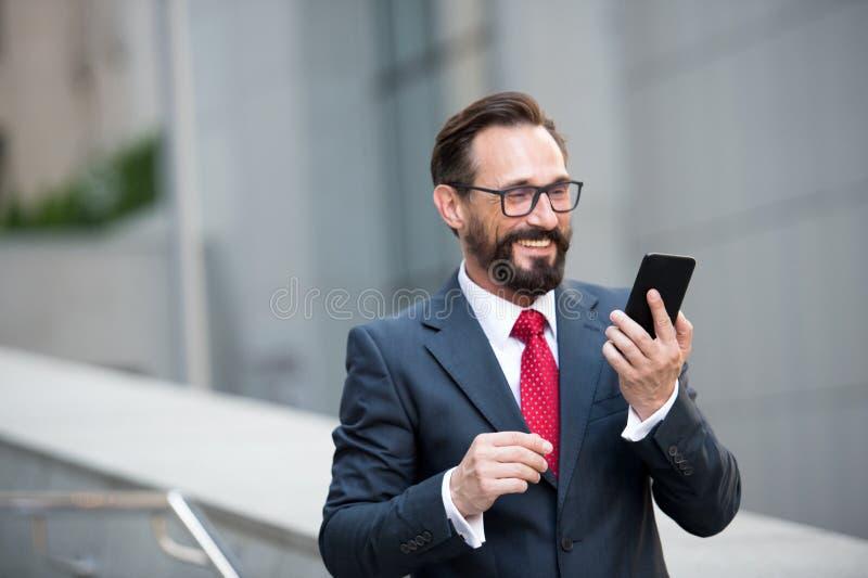 在玻璃的商人使用在办公室走道的巧妙的电话有城市大厦背景 商人的概念 库存照片