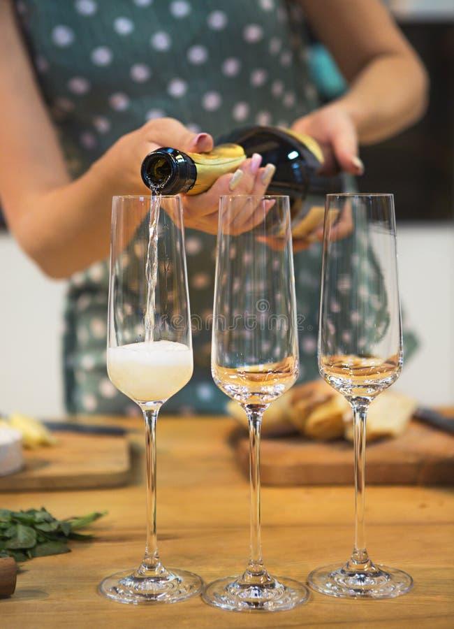 在玻璃的妇女倾吐的香槟与泡影 免版税图库摄影