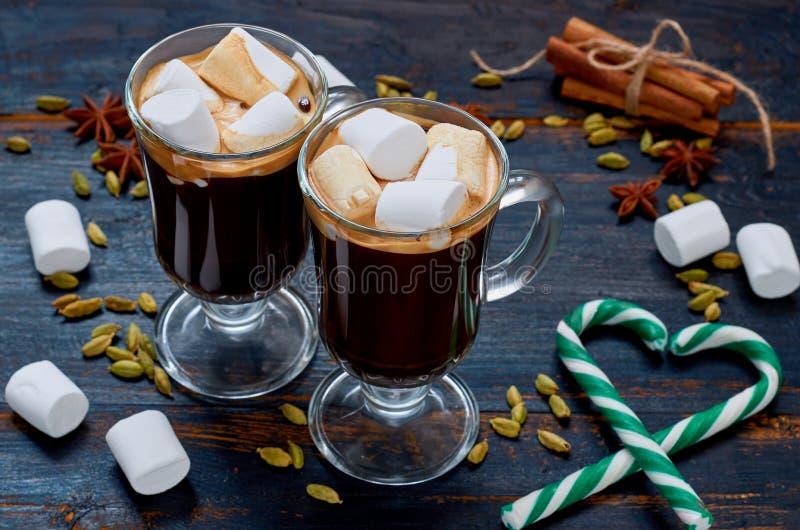 在玻璃的巧克力热饮用用绿色糖果锥体和冬天香料-桂香,豆蔻果实的心脏装饰的蛋白软糖 库存照片