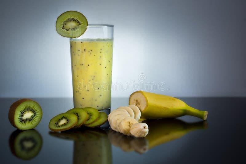 在玻璃的新鲜和水多的香蕉和猕猴桃圆滑的人用在-优质健康概念附近的果子在黑和灰色背景 库存图片