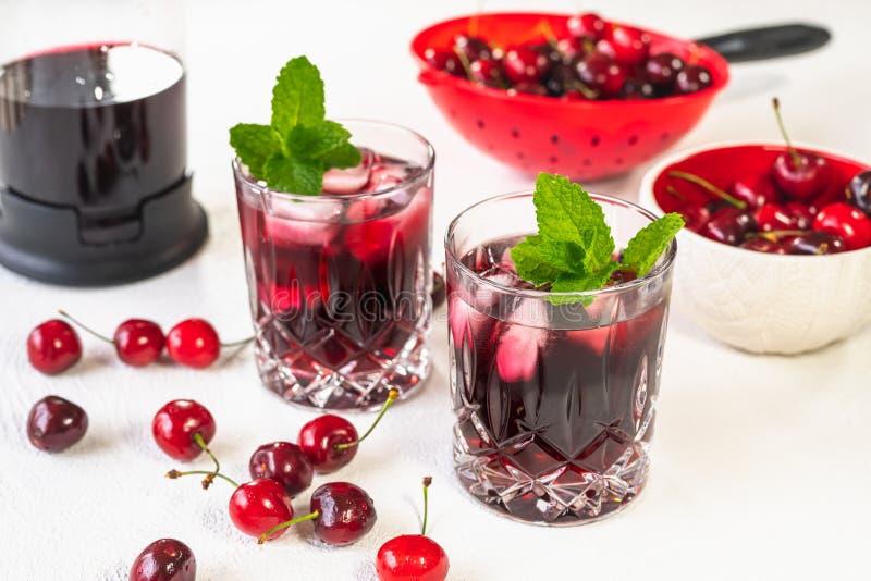 在玻璃的新鲜的冷的樱桃汁与薄荷叶和冰和樱桃在一个碗在白色背景关闭 库存照片