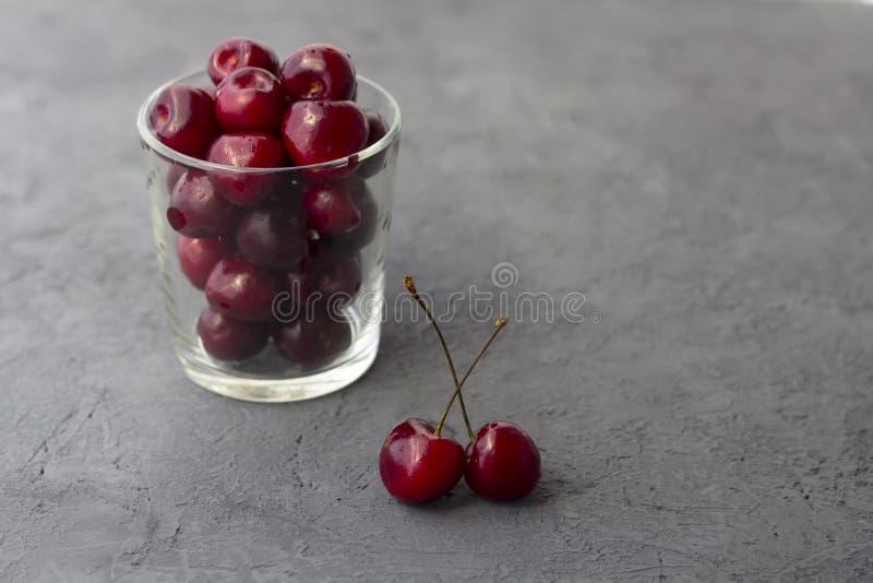 在玻璃的新鲜的有机成熟甜樱桃 免版税库存照片