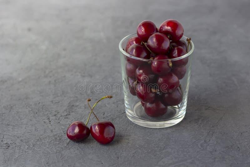 在玻璃的新鲜的有机成熟甜樱桃 库存图片