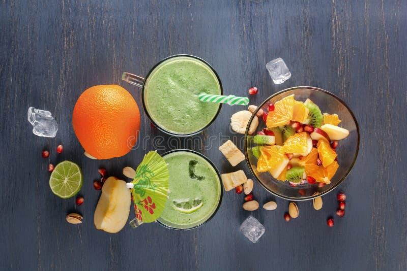在玻璃的新鲜的绿色圆滑的人抢劫水果、蔬菜和水果沙拉在一张木桌上与冰 图库摄影