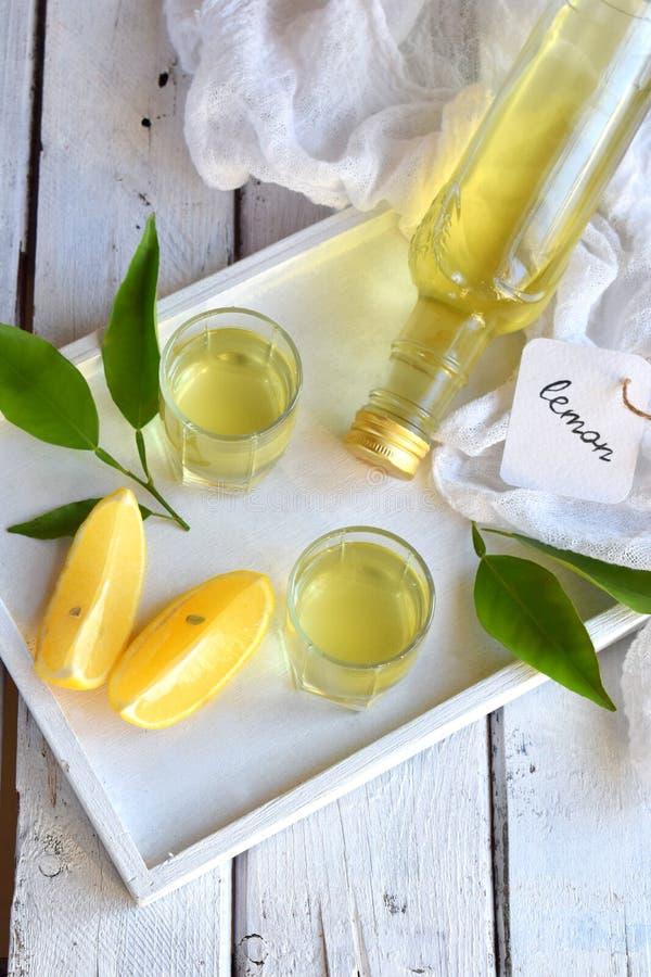 在玻璃的柠檬调味的意大利利口酒 可口黄色酒精饮料 Limoncello酒 玻璃瓶、射击和柑桔 C 库存照片