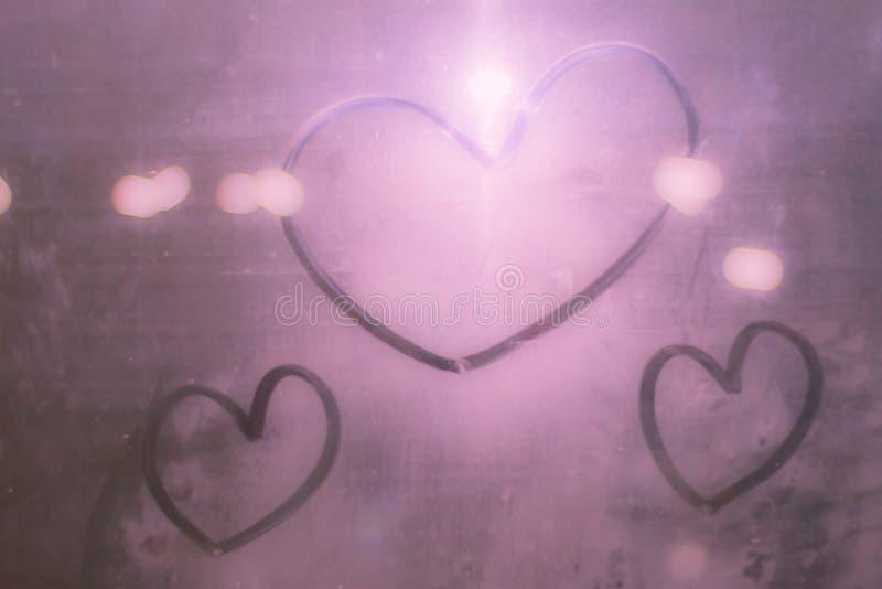 在玻璃的桃红色心脏从水 心脏bokeh美好或甜在背景的情人节 库存图片