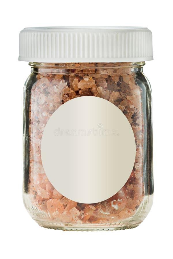在玻璃的热的熏制的辣椒盐与在白色背景的空的贴纸 库存照片