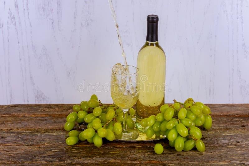 在玻璃的白葡萄酒与一束反对灰色木背景的绿色葡萄 免版税库存图片