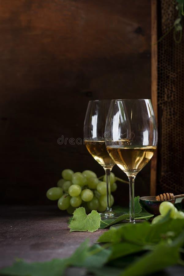 在玻璃的白酒 玻璃在一张黑暗的桌上站立在葡萄叶子和绿色葡萄旁边 蜂窝在背景中站立 图库摄影