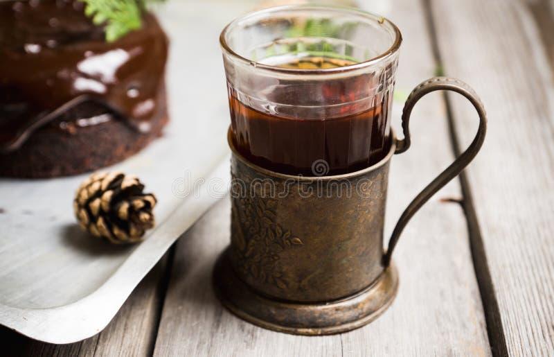 在玻璃的红茶与在土气背景的减速火箭的杯座 库存图片