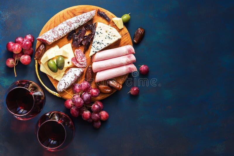 在玻璃的红葡萄酒,开胃菜,葡萄,冷盘,与霉的乳酪 在蓝色背景的熟食快餐 顶视图,拷贝sp 免版税库存照片