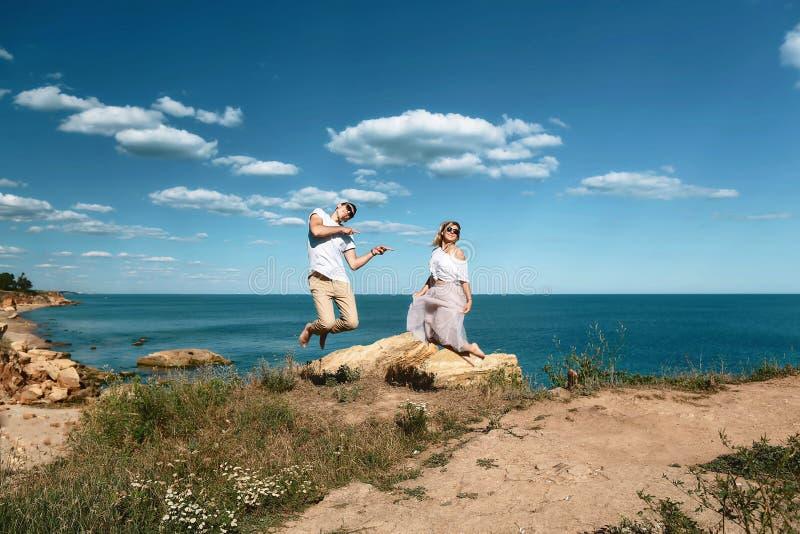 在玻璃的肉欲的年轻夫妇在岩石的爱跃迁在海滩附近的海与大峭壁 看在其中每一的男人和妇女 库存图片