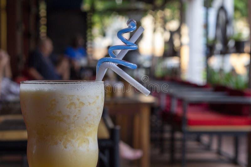 在玻璃的芒果震动与秸杆 在木桌上的乳状鸡尾酒 为饮料供食的黄色芒果圆滑的人 图库摄影