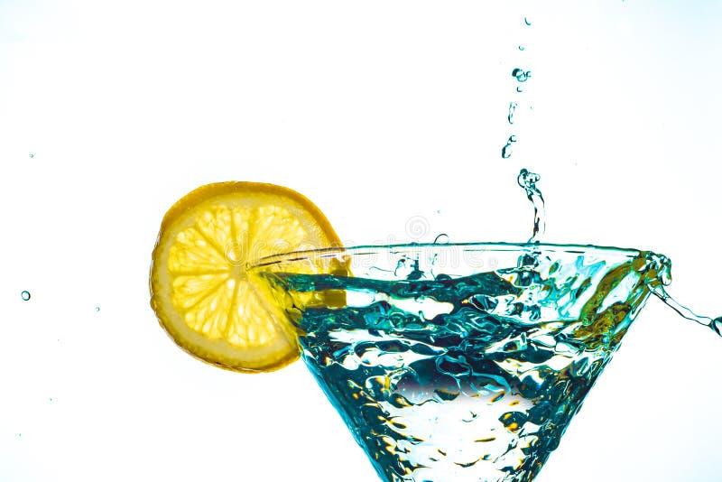 在玻璃的蓝色鸡尾酒水饮料飞溅用在白色隔绝的柠檬 库存图片