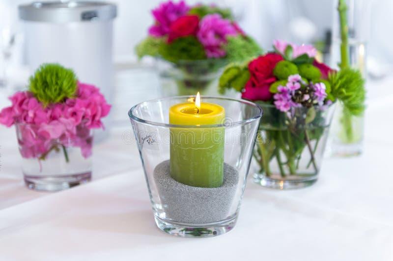 在玻璃的蜡烛在白色桌上 免版税库存图片