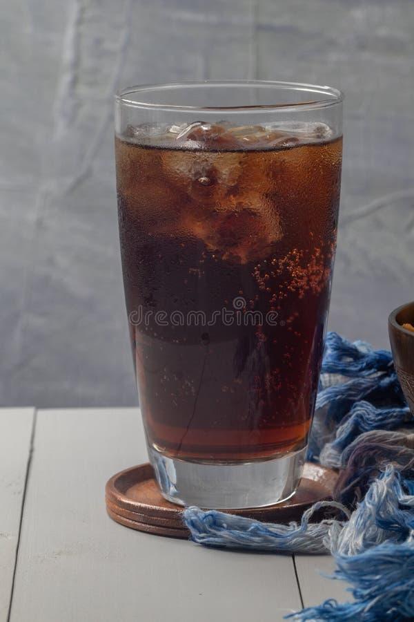 在玻璃的被冰的可乐在桌上 库存照片