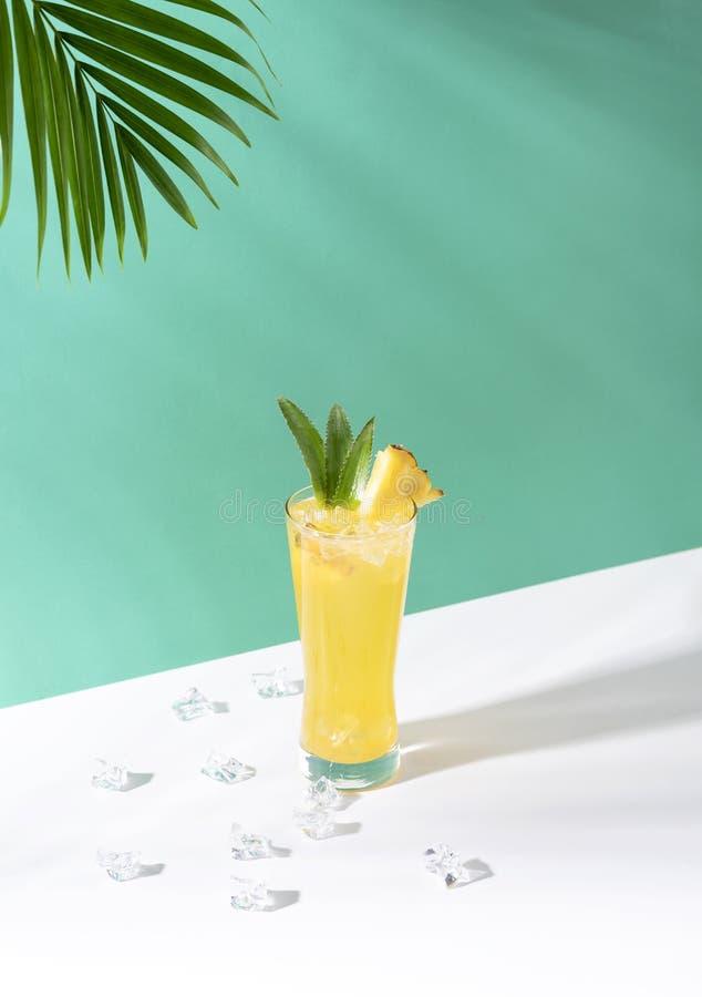 在玻璃的被冰的菠萝拳打鸡尾酒在绿色背景 夏天饮料 图库摄影