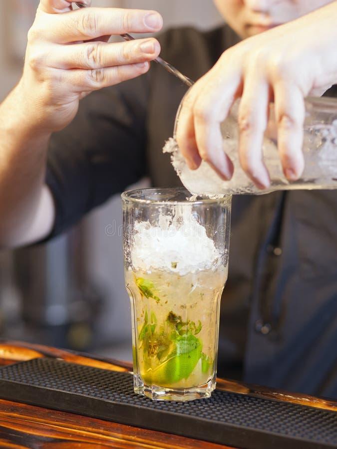 在玻璃的酒吧招待倾吐的冰 免版税库存图片