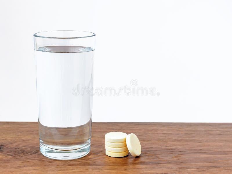 在玻璃的饮用水和在木背景的一些可溶解冒泡维生素药片与白色拷贝空间 维生素和 免版税库存图片