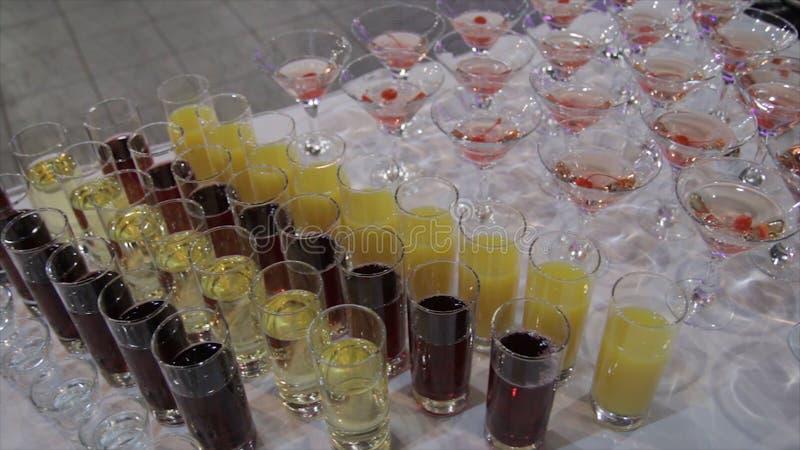 在玻璃的香宾用在桌和党背景的新鲜的樱桃 玻璃顶视图用不同的酒精饮料的 图库摄影