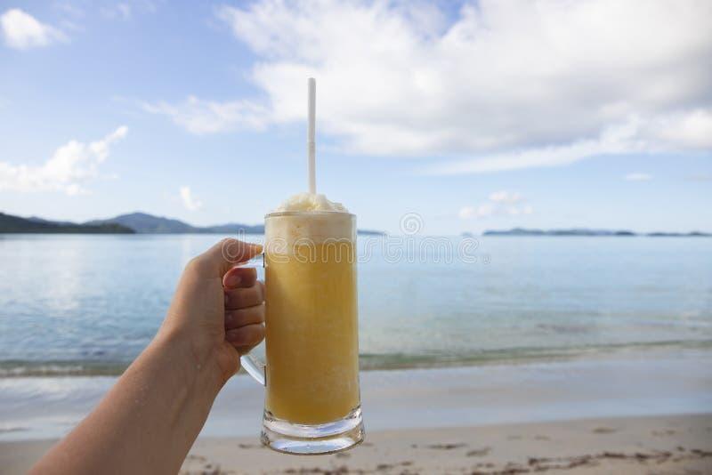 在玻璃的黄色芒果圆滑的人在热带海滩风景背景 节日快乐横幅模板 库存照片