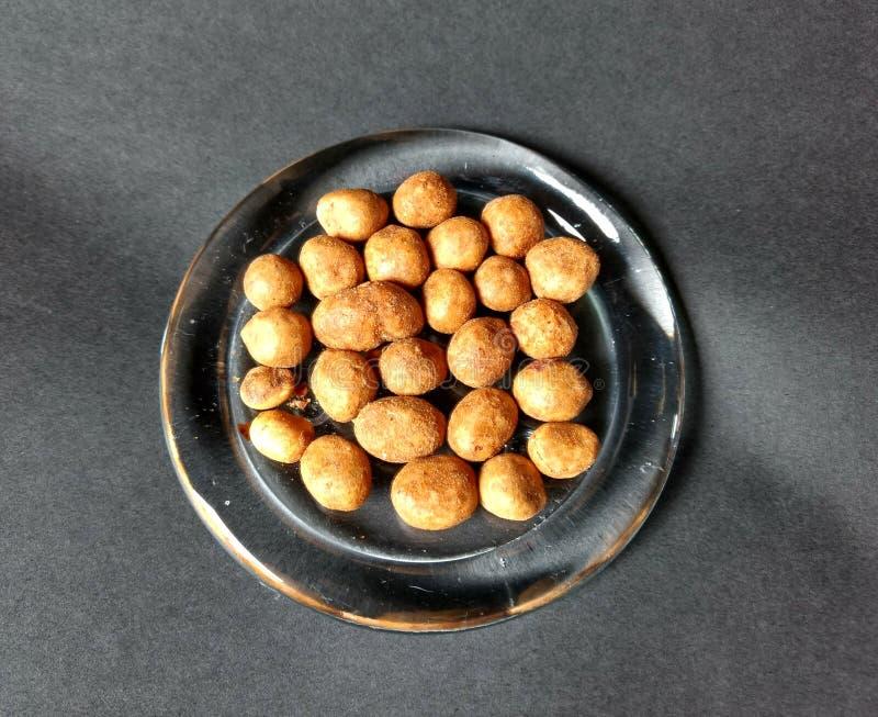 在玻璃盘供食的日本花生有黑背景 库存图片