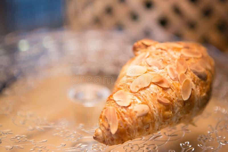 在玻璃盘的杏仁新月形面包 免版税库存图片