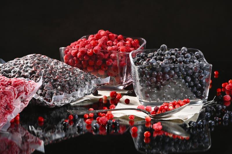 在玻璃碗的冷冻莓和蓝莓莓果 免版税库存图片