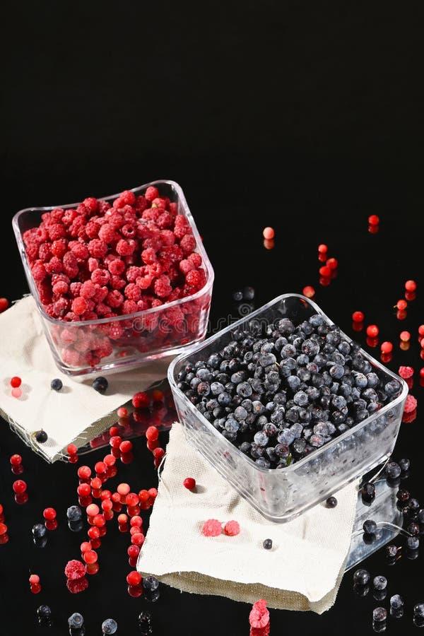 在玻璃碗的冷冻莓和蓝莓莓果 免版税库存照片