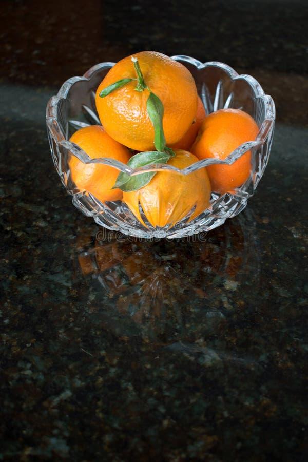 在玻璃碗的小桔子在花岗岩桌面 库存图片