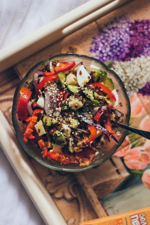 在玻璃碗的新鲜和可口鲜美健康沙拉在床上的陶瓷普罗旺斯样式盘子 免版税库存照片