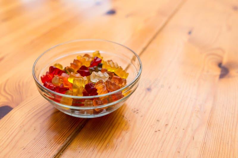 在玻璃碗的甜,可口胶粘的熊在射击的木桌关闭 库存图片