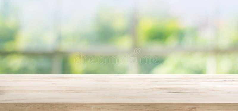 在玻璃窗和抽象绿色迷离的木台式从庭院 免版税库存图片