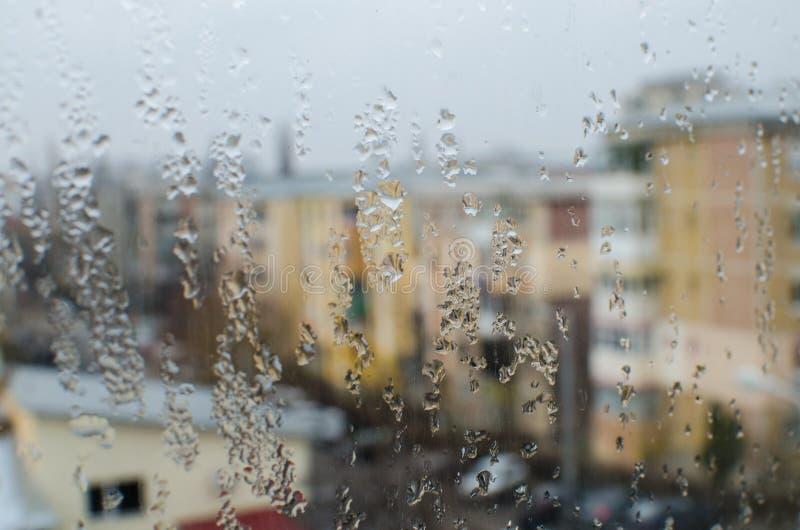 在玻璃窗的雨珠有大厦视图 免版税图库摄影