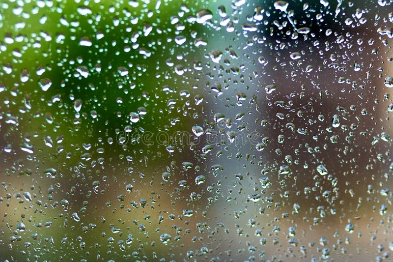 在玻璃窗的雨珠有迷离背景 免版税库存照片