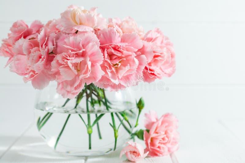 在玻璃花瓶的桃红色康乃馨在与拷贝空间的白色木背景 库存图片