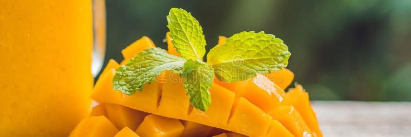 在玻璃金属螺盖玻璃瓶和芒果的芒果圆滑的人在绿色背景 芒果震动 热带水果概念横幅,长的格式 免版税库存图片