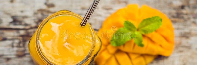 在玻璃金属螺盖玻璃瓶和芒果的芒果圆滑的人在绿色背景 芒果震动 热带水果概念横幅,长的格式 库存图片